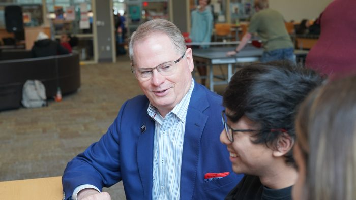 Dr. Stephenson smiling and talking with a student in the NWFSC Hangar at the Niceville campus.