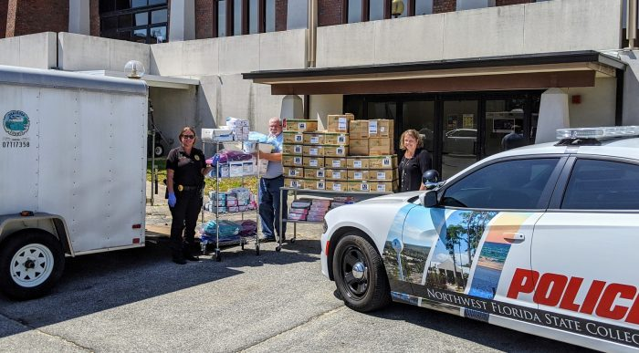 Sergeant Jo Culberson, NWFSC Campus Safety and Security and Dr. Charlotte Kuss, Dean of Health Sciences help load donations of personal protective equipment to Mr. Shayne Stewart, DOH Public Health Preparedness Branch Director