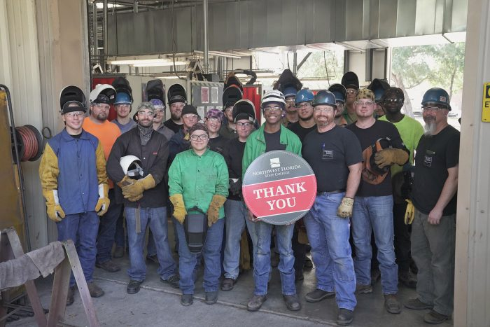 "Welding students hold ""Thank you"" sign"